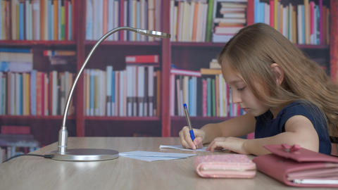 Student girl writing by pen on paper sheet on bookcase background. Girl teenager Live Action