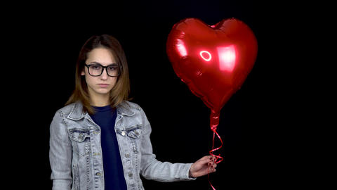 Sad young woman let go of heart-shaped balloon. A sad woman stands with helium Live Action