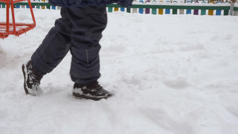Female legs dragging on snow path on winter walk. Legs of teenager girl in Live Action