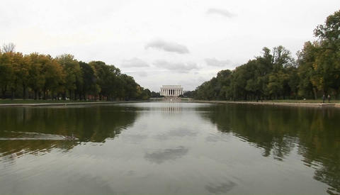 A long shot of the Lincoln Memorial across the reflecting pool with ducks swimming past Footage