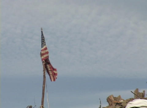 Zoom out from a flag planted in a pile of rubble left from Hurricane Katrina Footage