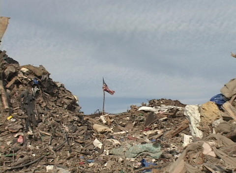 Zoom out from a flag planted in a pile of rubble left... Stock Video Footage
