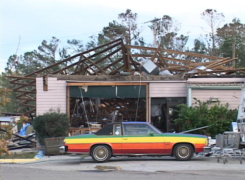 Medium shot of a rainbow colored car in front of a destroyed house Footage