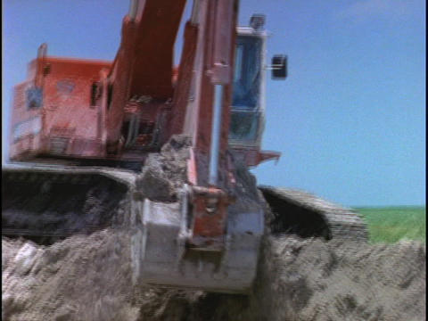 A steam shovel scoops and dumps dirt at a construction site Live Action