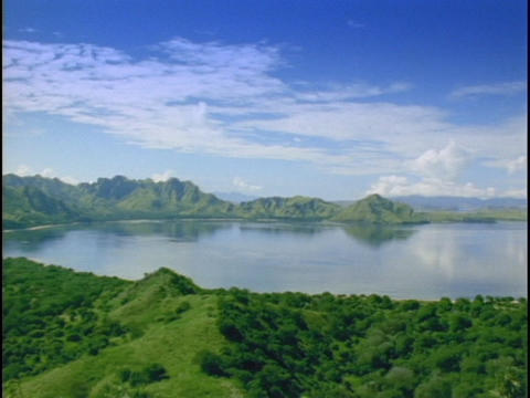 Lush mountains ring an island lagoon Stock Video Footage