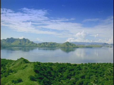 Lush mountains ring an island lagoon Stock Video Footage