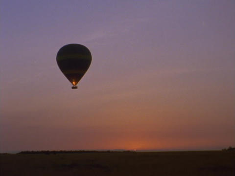 A hot air balloon floats over the savanna in Kenya, Africa Stock Video Footage