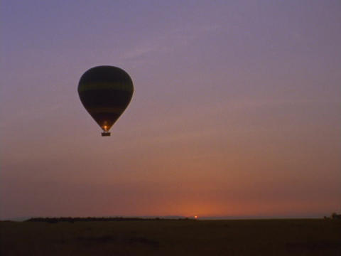 A hot air balloon floats over the savanna in Kenya, Africa Footage