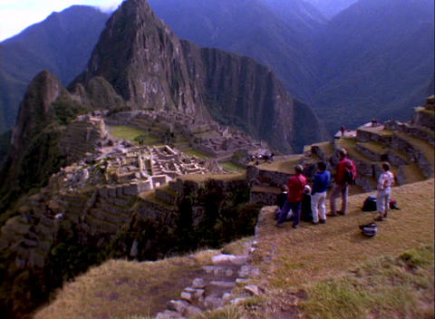 Wide-shot of tourists looking at Inca ruins of Machu Picchu in Peru Footage