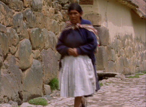 Lockdown of Peruvian woman walking down stone alleyway Footage