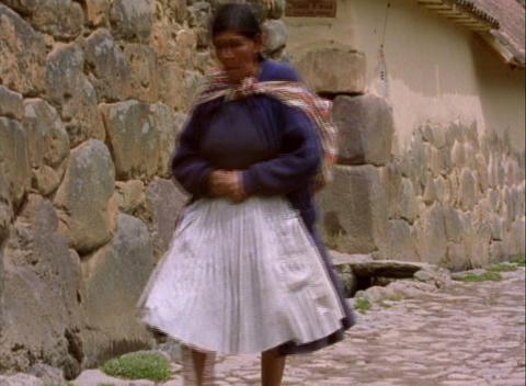 Lockdown of Peruvian woman walking down stone alleyway Stock Video Footage