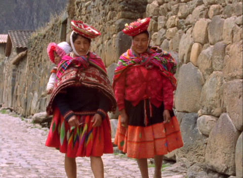 Hand-held shot of two Peruvian women walking along a cobblestone road in an ancient village Footage
