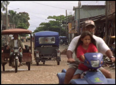Medium-shot of local people driving a variety of small vehicles on their village streets Footage
