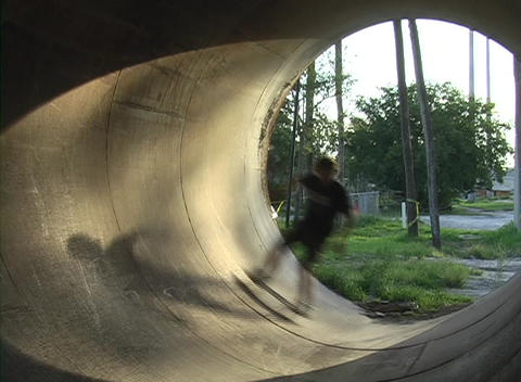 A skateboarder rides inside of a drainage tunnel Footage