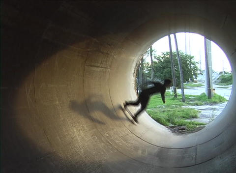 A skateboarder rides inside of a drainage tunnel Stock Video Footage