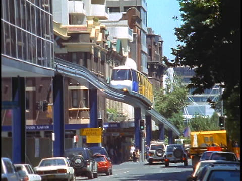 A monorail runs through downtown Sydney with street traffic below Footage