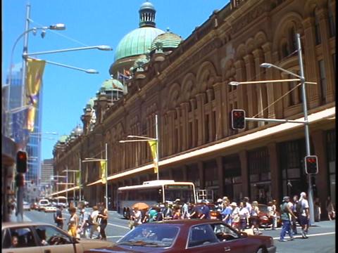 Pedestrians cross the street near an ornate building in downtown Sydney, Australia Footage