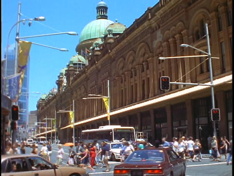 Pedestrians cross the street near an ornate building in... Stock Video Footage
