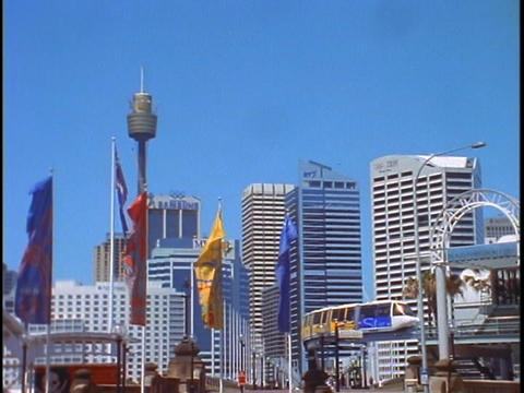 Flags blow in the breeze as the monorail travels away from the high rises of downtown Sydney, Austra Footage