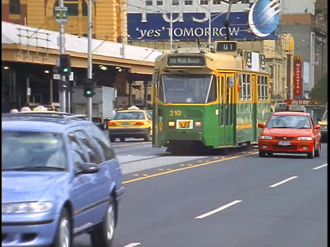 Cars pass a tram while traveling down a busy downtown... Stock Video Footage
