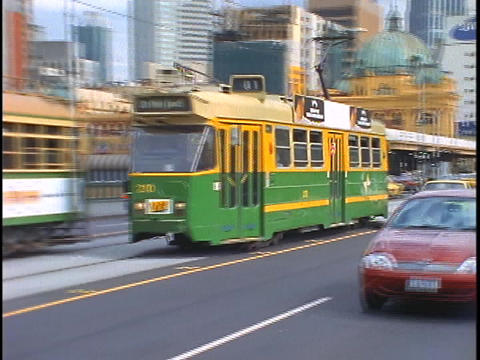 Cars pass a tram while traveling down a busy downtown street in Melbourne, Australia Footage