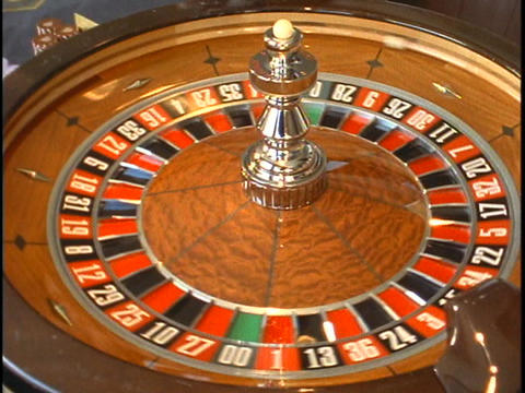 A ball rolls around the outside of a spinning roulette wheel Stock Video Footage