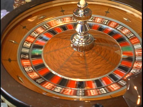 A ball rolls around the outside of a spinning roulette wheel Live Action