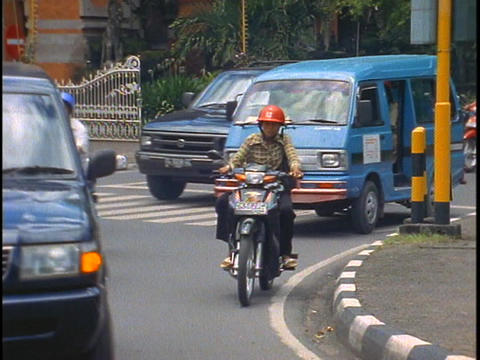Traffic passes through an intersection in Bali, Indonesia Stock Video Footage