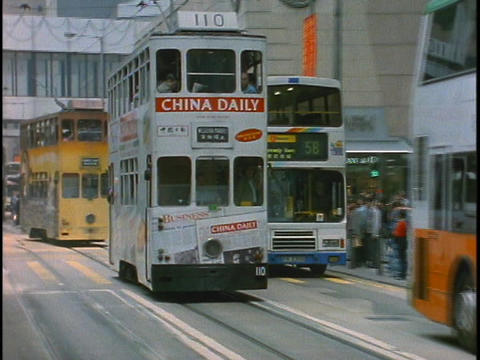 Double decker buses pass each other on a busy street in... Stock Video Footage