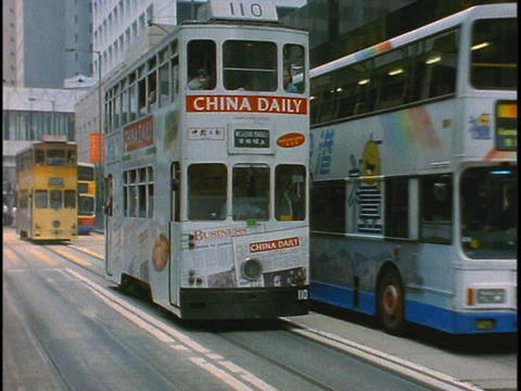 Double decker buses pass each other on a busy street in Hong Kong, China Footage