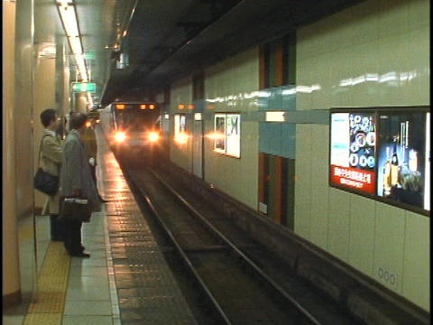 Commuters stand waiting for a subway train in Hong Kong Stock Video Footage