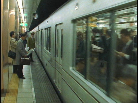Commuters stand waiting for a subway train in Hong Kong Footage