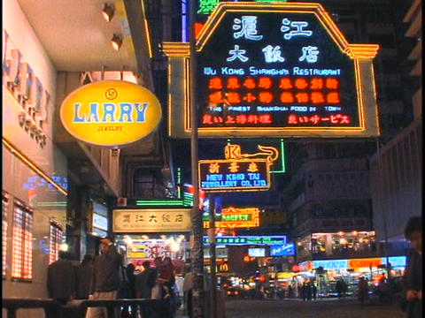 Pedestrians walk along a busy sidewalk in Hong Kong at night Stock Video Footage
