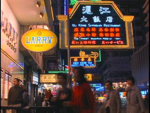 Pedestrians walk along a busy sidewalk in Hong Kong at night Stock Video Footage