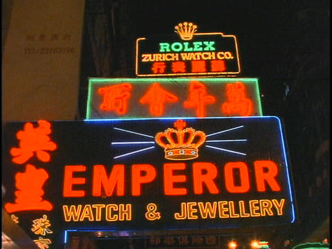 Buses drive beneath the Emperor Watch and Jewelry store neon-sign in Hong Kong Footage