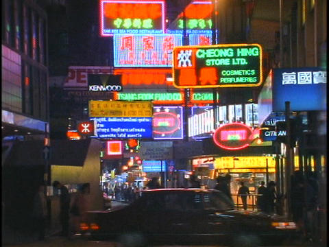 Buses, cars and pedestrian traffic passes by on a busy street in Hong Kong at night Footage
