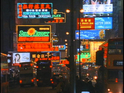 Heavy traffic passes by on a busy street in Hong Kong at night Footage