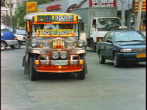 A jeepney drives down a street in Manila, Philippines Stock Video Footage
