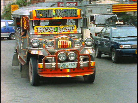 A jeepney drives down a street in Manila, Philippines Footage