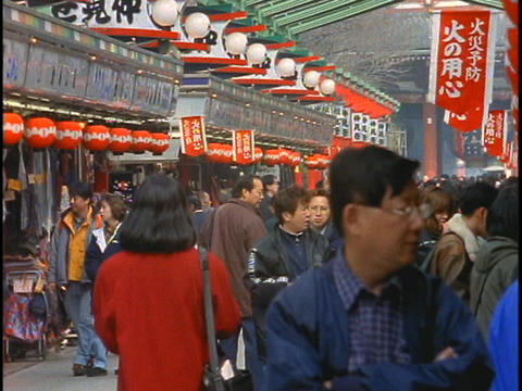 Shoppers walk along a shopping mall near a Buddhist Temple in Tokyo, Japan Footage