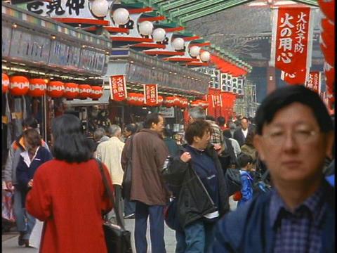 Shoppers walk along a shopping mall near a Buddhist... Stock Video Footage