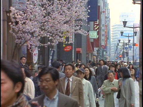 Crowds of pedestrians walk down a sidewalk in the Ginza... Stock Video Footage