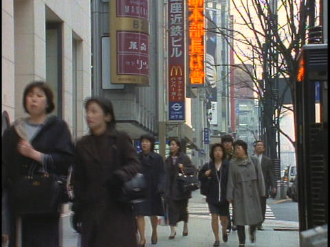 Crowds of pedestrians walk down a street in the Ginza... Stock Video Footage