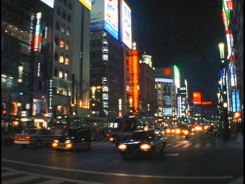 Heavy traffic drives below bright neon lights in Tokyo,... Stock Video Footage