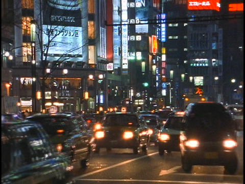 Heavy traffic drives down a street in the Ginza district... Stock Video Footage
