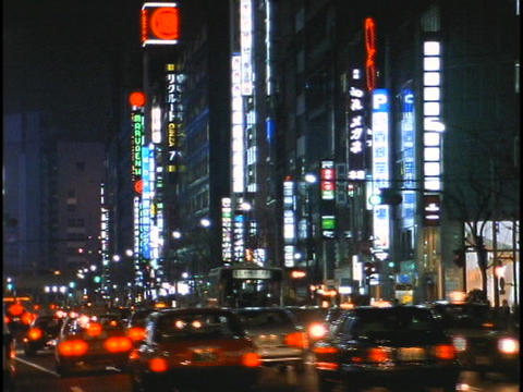 Traffic drives down a busy street in the Ginza district... Stock Video Footage