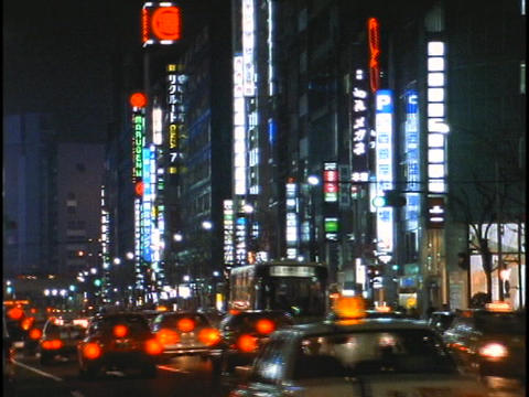 Traffic drives down a busy street in the Ginza district of Tokyo, Japan Footage
