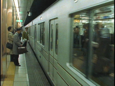 Commuters stand waiting to board an underground subway train Stock Video Footage
