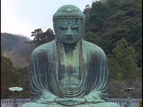 A giant Buddha sits in a garden in Kamakura, Japan Stock Video Footage