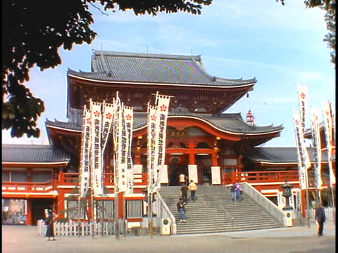 Worshipers walk into a Buddhist Temple in Japan Stock Video Footage